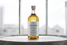 """AULTMORE: AULTMORE, part of the 'Last Great Malts of Scotland' collection from John Dewar & Sons. A rare Speyside malt known locally as """"a nip of the Buckie Road"""". The distillery's water filters down through the misty, mysterious 'Foggie Moss'. What more did we need as inspiration?"""