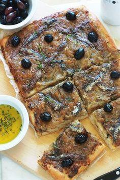La pissaladière, une recette niçoise avec une pâte à pain ou à pizza, oignons confits et ail, anchois et olives, des herbes aromatiques. Un régal pour les amateurs d'oignons et d'anchois.