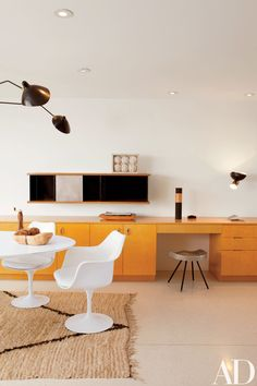 The kitchen in Vidal Sassoon's Bel Air retreat features a Saarinen Tulip table and chairs by Knoll and built-in cabinets by Neutra; the hanging cabinet and stool are by Jean Prouvé.