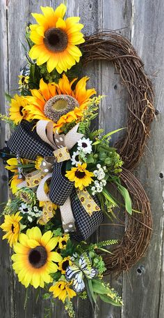 """XLarge Sunflower Grapevine Keep your Face to the sunshine & you cannot see the Shadow. It's what the Sunflowers do. XL 39"""" Length 24"""" Width Beauty is designed on double decker Grapevine base. Layered in different greenery of boxwood, long grassy yellow burst blooms and"""