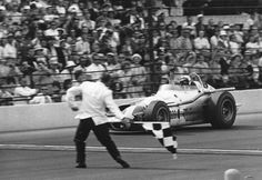 News Photo : A. J. Foyt takes the checkered flag to win his...