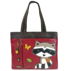 Chala Big Tote - Raccoon at The Handbag Store. Magnetic snap closure and zipper closure closure Chala Big Tote -Raccoon Burgundy with Detachable key chain with charm Character with detailed stitches Approx. Measurements: 15 x 3 x 13 in Handle drop: 9 in Magnetic snap closure and zipper closure for main Compartment Material: Textured faux leather. Color: Burgundy Shop in store at 253 Main St Hill City SD or online at www.shopthehandbagstore.com