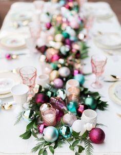 14 Festive Holiday Centerpieces That Will Make Your Table Pure Magic - How feminine and fun is this colorful ornament-filled runner? We'd throw away the holiday rulebook for this display!
