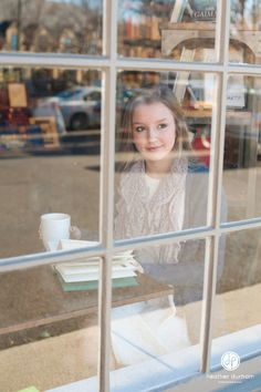 Senior portrait session in a coffee shop. Photo of highs school senior girl looking out a window. Birmingham, AL senior photography.  http://www.heatherdurhamphotography.com