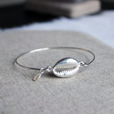 """A handmade bangle with a cowrie shell connector. All solid sterling silver. The bangle has been tumbled for hardness & shine. Logo tag is stamped B♥ (its round, not oval as shown). Extra Small: 2 1/4"""""""