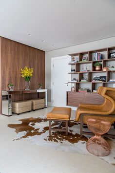 Parede com revestimento de madeira, poltrona com design criativo e aparador espelhado.