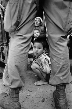 © Henri HUET / Associated Press Bong Son, octobre 1966. Une mère et ses enfants encadrés par les jambes d'un soldat américain.