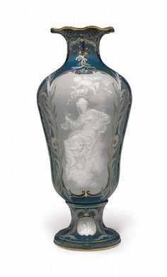 A MEISSEN PORCELAIN PATE-SUR-PATE BLUE AND DOVE-GREY GROUND VASE <br />CIRCA 1890, BLUE CROSSED SWORDS MARK, IMPRESSED MODEL NO. 383 AND 4, PROBABLY BY L. STURM<br />Of inverted pear form, with flaring frilled neck and rim, the front and back with shaped panels finely painted and hand-tooled in white slip, with nymphs and putti either spilling or stringing roses within a foliate scroll surround, the sides with elaborate trellis and diaper enclosing flowering branches and birds in flight, on…
