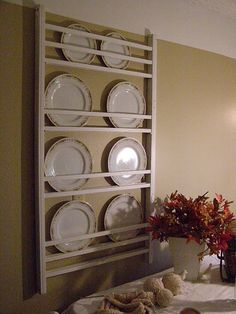 Plate display storage rack made from a repurposed crib side rail.  Remove some of the slats for size needed to hold plates. Upcycle, Recycle, Salvage, diy, thrift, flea, repurpose, refashion!  For vintage ideas and goods shop at Estate ReSale & ReDesign, Bonita Springs, FL