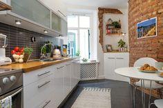 czarne płytki cegiełki na ścianie w kuchni pomiędzy białymi szafkami,czarna posadzka i ściana z czerwonej cegły przy białym stole kuchennym