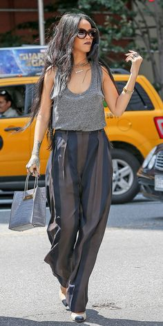 Rihanna wears a gray tank top, striped trousers, and a crocodile satchel
