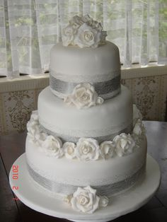 silver and cream wedding cake with roses | fruit cakes covered in marzipan and fondant, with white icing roses ...