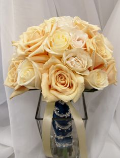 Two shades of ivory roses with marine blue fabric on the stems.