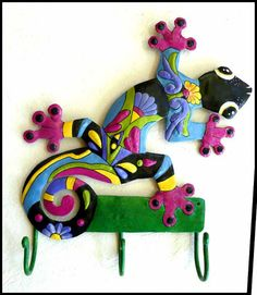 """Colorful, hand painted metal gecko. Looks good in your kitchen, patio or bathroom. Nice strong hooks. Hand painted on recycled steel oil drums. Gecko hook measures 12"""" x 15""""."""