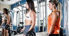 Para o bíceps, Nathália faz rosca direta. Com os braços esticados, segure a barra com as duas mãos