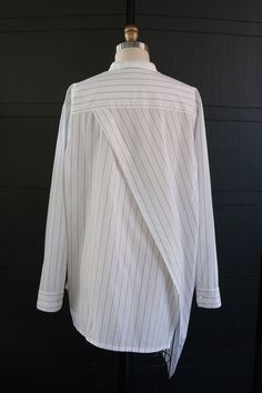 Modern seaming and angle play. Bright white cotton shirting with black pinstripe.