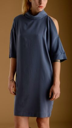 Three quarter blue silk dress characterized by one loose fitting sleeve and a open sleeve, turtle neck, key-hole detail with button at back, two welt pockets at front, comfort fit, knee lenght, 92% silk 8% elastan.