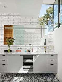 This master bathroom has a high window allowing light and privacy and a contrast of modern cabinetry with classic subway and decorative concrete tile. A floral floor pattern brings life into the all white modern design.