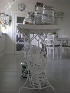 Une vieile table de machine à coudre Singer repeinte en blanc par exemple