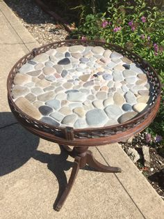 This is a vintage table that I have had for sometime that I decided to cover in flat beach stone rocks from Lake Erie. It is a one of a kind