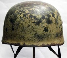 This reproduction helmet is based on the Afrika campaigns of World War Two. It has dark Luftwaffe apple green grey base paint and then a sand coloured camouflage top paint. The paint has aged during and worn during combat as well as over the years. It has the early model steel liner retaining bolts. The inner lining is very well maintained yet aged, again to reflect the period of use and 60+ years of ageing. The lining rubber is fully intact.