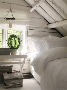 small white bedroom, exposed wood beams / planks painted white, white desk next to bed serves as a nightstand / bedside table, stacks of magazines under the desk