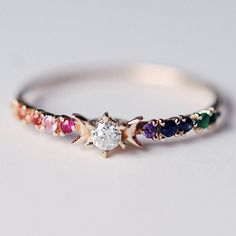 "Inspired by the E.E. Cummings quote, ""you are my sun, my moon, and all my stars..."" this ring captures the whimsy of his poetry. Featuring a dazzling array of rainbow stones surrounding a center diamond and set in solid 14K yellow gold. Each ring box is engraved with the quote, allowing you to ca..."