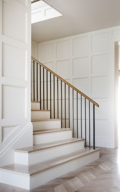 The entry features a classic herringbone pattern on the floors while the paneling detail adds warmth. We love how the simple baluster design keeps the focus on the trim details | Coats Homes | Highland Park, TX