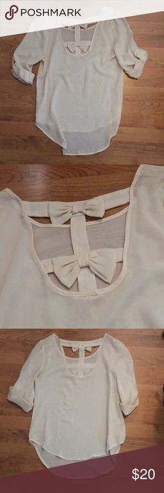 Cream shirt with back bow detail Super cute cream colored shirt, high low style. Two bows on the back to spice it up! 3/4 sleeve that can be rolled up and buttoned. Work a few times but still in great condition! No runs. 100% polyester. Size small, bought from Windsor. Windsor Tops Blouses
