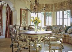 Meals are enjoyed at this dining table that boasts great views provided by a large bay window. Earth tones bring the area together, while an elegant chandelier provides light after the sun has set. Classic drapes blend well with the ornately finished dining chairs to keep the room traditional.