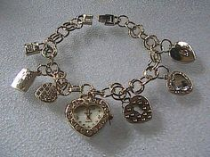Brand New without tag Silver Tone Quartz Watch Bracelet, 7 different lovely charms including the watch, weigh 57.1 grams, 9 inches long, very nice clasp.