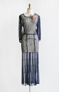1930s midnight navy sheer lace gown with long  puff sleeves. Vintage 30s dress has soft square neckline, buttons along the back neck, slightly extended shoulders, and light flare to the hem of the skirt. Dress comes with pink purple flowers that you can pin at the shoulder (as shown) or on the waist.
