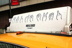 """John & Yoko's """"War is Over""""      in sign language on a NYC taxi."""
