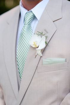 Khaki suit, light green tie, orchid boutonniere. Great for summer! If there is green bridesmaid dresses, this would be a great look for the men.