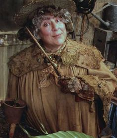 Miriam Margolyes is Pomona Sprout,  Professor of Herbology and the Head of Hufflepuff House. She is described as often covered in dirt due to the time she spends tending plants in the Hogwarts greenhouses.  She teaches her second year students to work with Mandrake plants. She is responsible for raising the Mandrakes to full maturity, at which point their juice is used to revive the petrified victims of the basilisk.