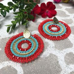 Add a pretty pop of color to your outfit with the Mariana Drop Earring. Bright red and turquoise beads and gold accents forms these fun and festive hoop earrings. surgical steel post back Handcrafted by Treasure Jewels in Columbia Fair Trade Embroidery Jewelry, Hand Embroidery, Crochet Earrings, Beaded Earrings, Beading Patterns Free, Bead Crochet Rope, Jewelry For Her, Simple Earrings, Turquoise Beads