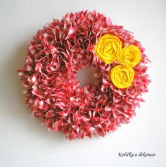 U tří žlutých růží Dekorační věnec, vytvořený technikou vypichování z červeno a růžovo bíle kostičkované bavlněné látky, dozdobený třemi čajovými růžemi ze žluté stuhy. Průměr věnce je 30 cm.