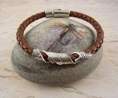 Artisan Fine Silver Brown Trout Leather Bracelet  by carolannbosek.etsy.com  I used my own carving of a brown trout to create this fine silver fish which I wrapped around braided leather cord and finished with a sterling silver-plated magnetic clasp!