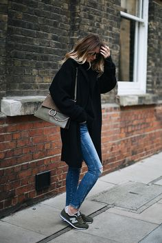 Emma Hill wears black winter coat, ripped skinny jeans, khaki new balance trainers, khaki Chloe Faye bag, casual weekend winter outfit