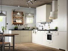 An off-white country kitchen with black worktops. Combined with off-white oven and extractor hood.