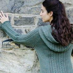 A cabled raglan hooded cardigan by Alison Green.Lovely but simple cable and slipped stitch panels add a beautiful detail to this cosy hooded cardigan. The back