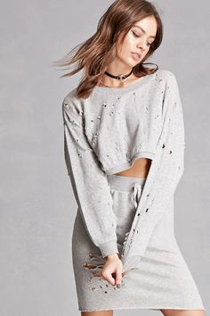 A French terry knit cropped sweatshirt featuring a crew neck, allover distressing, dropped shoulders, long sleeves, and ribbed trim. Matching skirt available. This is an independent brand and not a Forever 21 branded item.