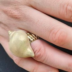 Vintage 80s gold tone sea shell ring.  Amazing condition.  Fits most sizes due to elasticated band.  *We aim to sell items in the best possible condition, however most of our stock is vintage and therefore secondhand and may have some signs of wear. Any major flaws will be noted in description and highlighted in photos to the best of our ability*