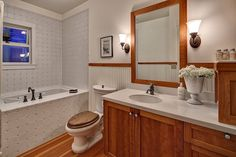 Craftsman Full Bathroom with Undermount Sink, Wainscoting, Wall sconce, Hardwood…