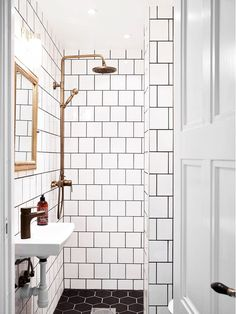White tiled shower with brass fixtures.