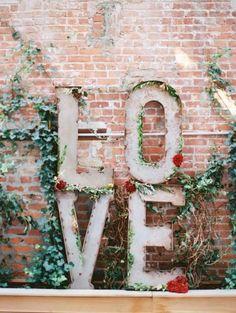 LOVE decor against wall backdrop | Wedding Reception Backdrops via http://emmalinebride.com/decor/wedding-reception-backdrops/