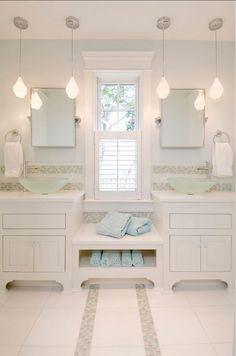White tile bathroom with cute lamps and elegant cabinets