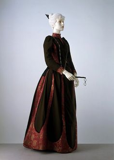 Day Dress, side view. Charles Frederick Worth, Paris, ca. 1889. Wool, with figured satin panels, edged with silk braid. With its minimal bustle and strong emphasis on the sleeves, this day dress illustrates the smoother silhouette that began to appear in the late 1880s. It is said to have been worn by Cara Leland Huttleston Rogers of New York, later Lady Fairhaven. Victoria & Albert Museum, London, England, UK. Museum no. T.268. Given by Lord and Lady Fairhaven.