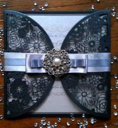A beautiful invitation with arc shaped gate fold floral cut front made from pearlescent black card stock. The insert is pearlescent