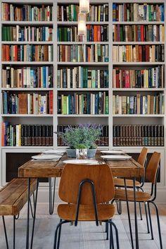 Esstisch mit Bank & Stühlen aus Holz sowie Lavendel auf dem Tisch. Dahinter großes Buchregal.